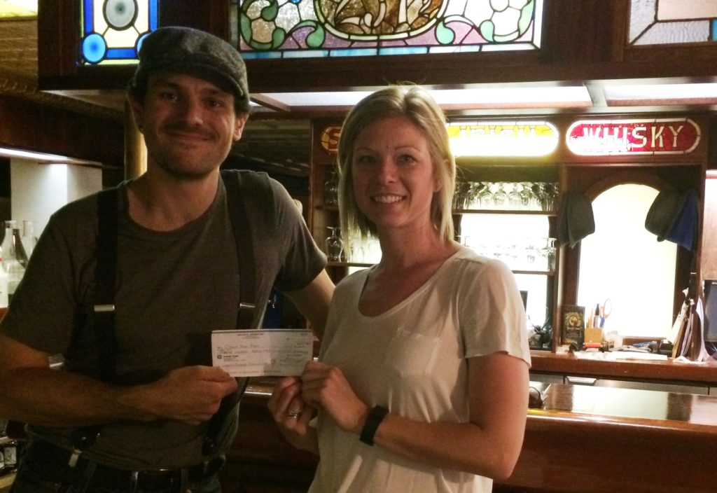 Marc-Andre Chainey of Waller Street Brewing presenting donation to Ottawa Food Bank's Samantha Ingram